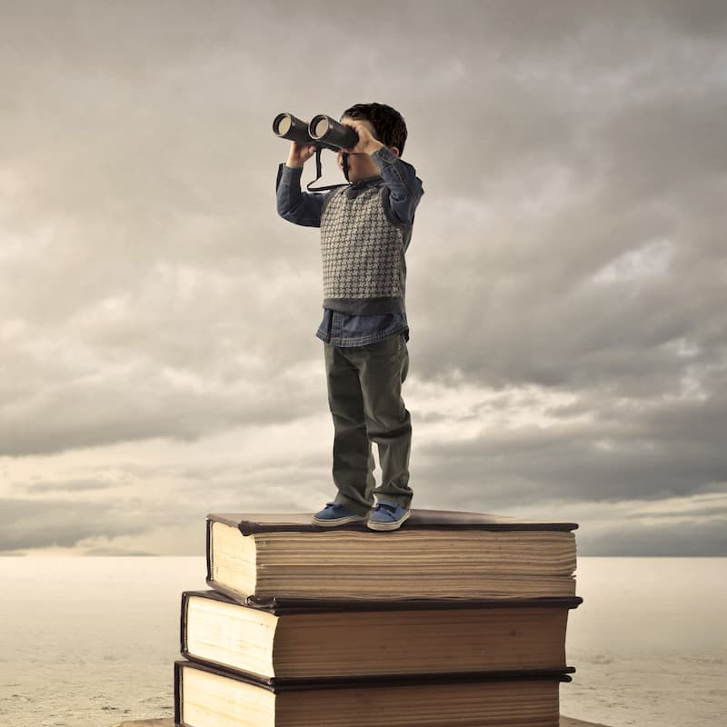 Boy standing on books looking through binoculars.